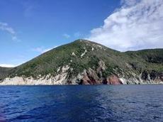 Rostfärgade berg längs insegling till Portoferrario