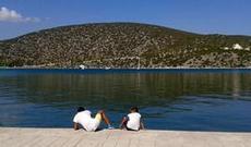 Två pojkar kikar efter fisk i hamnen Ermioni