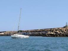 En segelbåt på grund i hamninloppet i Mazagon